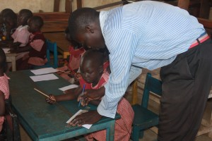 St Kizito Denis helping a pupil