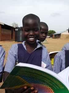 Betty Alum 12 years old in Primary 3 is very excited to see a pupil's text book for the first time in their school.